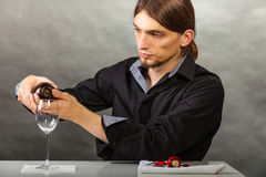 Wine steward fills glass. Alcohol liquor drinking tasting relax concept. Wine steward fills glass. Young male waiter pours drink into cup Stock Images