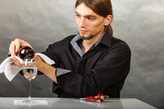 Wine steward fills glass. Alcohol liquor drinking tasting relax concept. Wine steward fills glass. Young male waiter pours drink into cup Stock Image