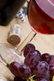 Wine still life. A stylish angled view of fresh grapes with a glass of red wine royalty free stock photo
