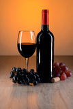 Wine still life. Bottle of red wine on wooden table with beautiful reflections Royalty Free Stock Photo