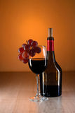 Wine still life. Bottle of red wine on wooden table with beautiful reflections Stock Images