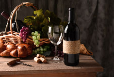 Wine Still Life. On a rustic wood table with warm afternoon window light. An old fashioned cork screw, a basket of grapes and leaves, a loaf of bread and some stock image