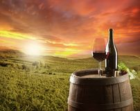 Wine. Still life on wooden keg with vineyard on background Stock Photo
