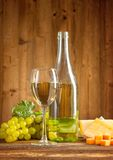 Wine. Still life on wooden keg with vineyard on background Royalty Free Stock Image