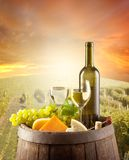 Wine. Still life on wooden keg with vineyard on background Stock Image