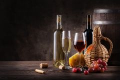 Wine still life on a wooden table. Bottles, glasses, barrel and grapes with cheese on a wooden table Royalty Free Stock Photography