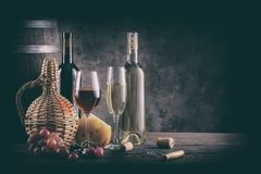 Wine still life on wooden table. Processing for vintage. Bottles, glasses, barrel and grapes with cheese on a wooden table Stock Image