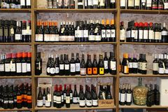 Wine Store. Close up of many various wine brand bottles in a wooden stand against a light brick background in Barcelona, Spai stock images