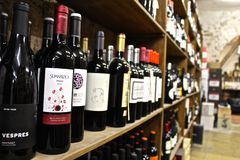 Wine Store. Perspective shot of many various wine brand bottles in a wooden stand against a light brick background in Barcelona, Spain with Sumarroca and Vespres stock photos