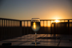 Wine at Sunset. Glass of wine on a tile table reflecting the sunset royalty free stock photo
