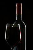 Wine symmetry. Red wine bottle with wineglass on a black background with rim light royalty free stock photos