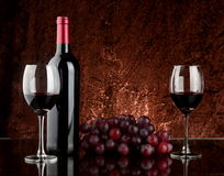 Wine on table. A bottle of red wine, two full glasses and a bunch of grapes on dark table Stock Photo