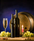 Wine table set. Two wine bottles, a glass, some grapes and a barrel royalty free stock photo