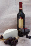 Wine tasting. Bottle and glass of wine with grapes and cheese Royalty Free Stock Photo
