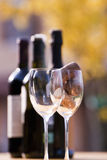 Wine tasting. Four bottles of wine and two empty glasses, one with some corks in, ready for the wine tasting;all outside. Vertical picture stock images