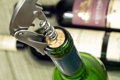 Wine tasting. Corkscrew wrapped in cork bottles of wine royalty free stock photography