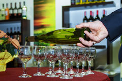Wine Tasting. The waiter pours white wine in a wine glass for wine tasting Royalty Free Stock Images