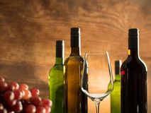 Wine tasting atmosphere in a winery cellar with an empty wine glass and wine bottles Royalty Free Stock Images