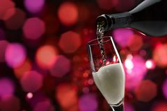 Wine tasting and celebration. Pouring sparkling white wine into a wineglass, wine tasting and celebration concept royalty free stock images