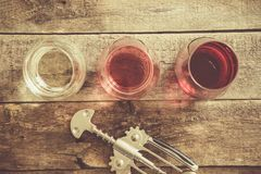 WIne tasting concept - red, rose and white wine in glasses. On wood background stock photo