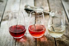 WIne tasting concept - red, rose and white wine in glasses. On wood background royalty free stock image
