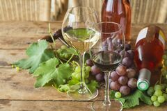 Free Wine Tasting Concept. Two Glasses Of Red An White Wine, Grapes And Two Bottles Of Pink Royalty Free Stock Image - 169791666