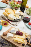 Wine tasting. High angle view of dinner table with cheese, salad and wine Stock Images