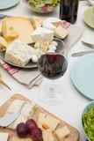 Wine tasting. High angle view of dinner table with cheese, salad and wine Stock Photos
