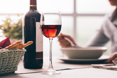Wine tasting at the restaurant. Woman having lunch at the restaurant and drinking a glass of red wine, fine dining and wine tasting concept royalty free stock image