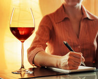 Wine tasting. Sommelier making notes in notebook Royalty Free Stock Images