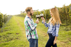 Wine tasting in the vineyard. Young happy couple holding glasses of wine in the grape fields Royalty Free Stock Images