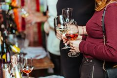 Wine tasting: visitors stand near tables with tasting samples and hold glasses. Of wine stock photos