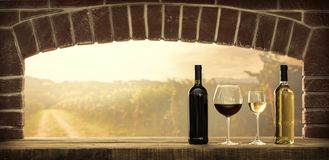 Wine tasting in the cellar. Wine tasting in the wine cellar: red and white wine bottles, wine glasses and panoramic view of the countryside vineyards at sunset Stock Photography