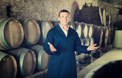 Wine technician working in storage with wooden barrels Stock Photo