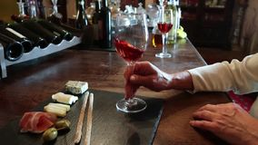 Wine test, crystal glass, red wine, cheese, bar counter background. Glasses of wine and cheese plate. Wine testing. Wine test, crystal glass, red wine, cheese stock footage