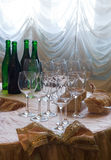 Before wine testing. Wine glasses are in the foreground, Lot of wine bottles is in the background. It's all taped for wine testing Royalty Free Stock Photography