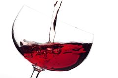 The wine to flow in a glass. The red wine to flow in a glass. Isolated white Royalty Free Stock Photos