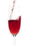 The wine to flow in a glass. The red wine to flow in a glass. Isolated white Royalty Free Stock Photography