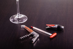 Wine tools on table. A glass of wine and some wine tools on a dark wooden surface Stock Photos
