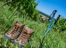 Wine Tourism-Pair of hiking shoes in the grass surrounded vineya Royalty Free Stock Photos