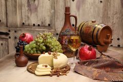 Wine in a transparent glass, grapes and red pomegranate Stock Photos
