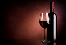 Wine on vinous background. Red wine in bottle and wineglass on vinous background Stock Image