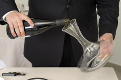 Wine waiter decantering a bottle of red wine Royalty Free Stock Photography