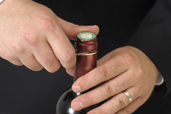 Wine waiter opening a bottle of red wine Stock Images