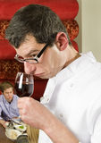 Wine waiter savouring wine. Wine waiter savoring wine in a restaurant witch customers on the background stock images