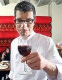 Wine waiter savouring wine. In a restaurant witch customers on the background stock images