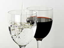 Wine and water. Splashing water on a glass and a cup of wine on a white background Stock Photography