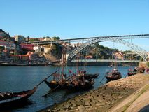 Wine and water. A group of typical boats on the Douro river in front of the docks of Villa Nueva de Gaia with the Ribeira and Eiffel's bridge on the background Royalty Free Stock Image