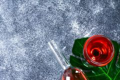 Wine in a wineglass, a bottle and a tropical leaf. Top view. Wine drink on a gray background. Copy space. Wine in a wineglass, a bottle and a tropical leaf. Top stock images