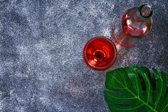 Wine in a wineglass, a bottle and a tropical leaf. Top view. Wine drink on a gray background. Copy space. Wine in a wineglass, a bottle and a tropical leaf. Top royalty free stock photo